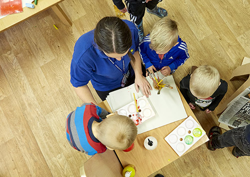 nursery worker drawing with children around a table